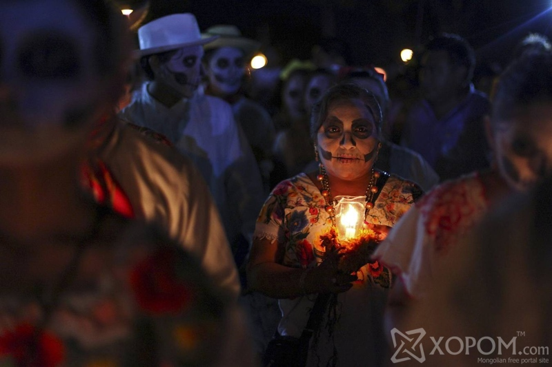 """A woman, with her face painted as a skull, holds a candle while taking part in a traditional parade called """"Paseo de las Animas"""", or Parade of Souls, as part of Day of the Dead celebrations in Merida, Mexico, October 31, 2015. REUTERS/Lorenzo Hernandez"""