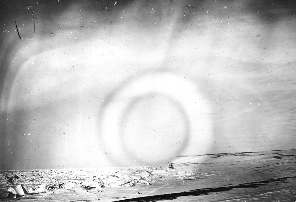 The Aurora Borealis, a luminous phenomenon, otherwise called the 'Northern Lights' is viewed over the Arctic, photographed by members of the British Nares expedition. Their ship can be seen trapped in sea ice in the bay. (Photo by Hulton Archive/Getty Images)